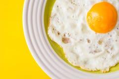 Τηγανισμένο αυγό στο άσπρος-πράσινο πιάτο στο κίτρινο υπόβαθρο Στοκ φωτογραφία με δικαίωμα ελεύθερης χρήσης