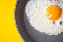 Τηγανισμένο αυγό στο τηγάνισμα του τηγανιού στο κίτρινο υπόβαθρο Στοκ Φωτογραφίες