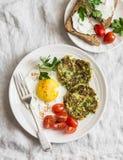Τηγανισμένο αυγό, fritters κολοκυθιών και σάντουιτς τυριών κρέμας - εύγευστο πρόγευμα, brunch ή πρόχειρο φαγητό Σε μια ελαφριά αν στοκ εικόνες