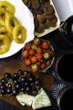 τηγανισμένο καλαμάρια ή calamari χταποδιών με το σταφύλι, ξηρό βερίκοκο, φράουλα, μπουκάλι του κόκκινου κρασιού, γυαλί δύο στοκ εικόνες