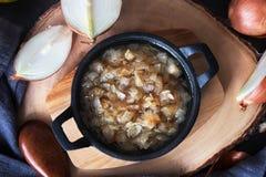 Τηγανισμένο κρεμμύδι σε ένα τηγανίζοντας τηγάνι σε έναν ξύλινο πίνακα Στοκ εικόνες με δικαίωμα ελεύθερης χρήσης