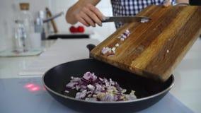 Τηγανισμένο κρεμμύδι στο πετρέλαιο σε ένα τηγανίζοντας τηγάνι συνδετήρας Ο χορτοφάγος ανακατώνει τα τηγανητά κατανάλωση υγιής Τοπ απόθεμα βίντεο