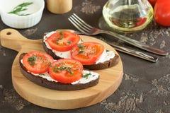 Τηγανισμένο μαύρο ψωμί με το τυρί, τις ντομάτες και τα πράσινα για το μεσημεριανό γεύμα Στοκ εικόνες με δικαίωμα ελεύθερης χρήσης