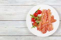 Τηγανισμένο μπέϊκον, ντομάτες, arugula στο πιάτο Στοκ εικόνες με δικαίωμα ελεύθερης χρήσης