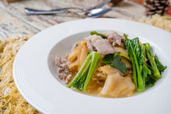 Τηγανισμένο νουντλς με το χοιρινό κρέας και κατσαρό λάχανο που ενυδατώνεται στο ζωμό Στοκ Εικόνες