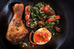 Τηγανισμένο πόδι κοτόπουλου σε ένα μαύρο πιάτο με μια σαλάτα, ένα αυγό και μια σάλτσα ντοματών Μεσογειακή κουζίνα Στοκ Φωτογραφίες