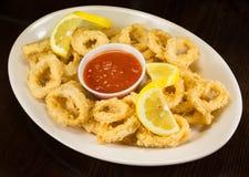 Τηγανισμένο Calamari με την κόκκινη σάλτσα ντοματών και λεμόνι σε ένα πιάτο Στοκ Εικόνες