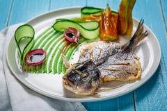 Τηγανισμένο dorado ψαριών, που διακοσμείται με τα αγγούρια και τα κρεμμύδια Σε ένα μπλε ξύλινο υπόβαθρο Στοκ Εικόνες