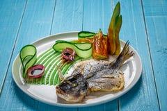 Τηγανισμένο dorado ψαριών, που διακοσμείται με τα αγγούρια και τα κρεμμύδια Σε ένα μπλε ξύλινο υπόβαθρο Στοκ φωτογραφίες με δικαίωμα ελεύθερης χρήσης