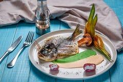 Τηγανισμένο dorado ψαριών, που διακοσμείται με τα αγγούρια και τα κρεμμύδια Σε ένα μπλε ξύλινο υπόβαθρο Στοκ Φωτογραφία
