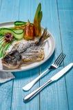 Τηγανισμένο dorado ψαριών, που διακοσμείται με τα αγγούρια και τα κρεμμύδια Σε ένα μπλε ξύλινο υπόβαθρο Στοκ Φωτογραφίες