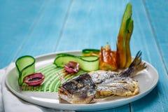 Τηγανισμένο dorado ψαριών, που διακοσμείται με τα αγγούρια και τα κρεμμύδια Σε ένα μπλε ξύλινο υπόβαθρο Στοκ φωτογραφία με δικαίωμα ελεύθερης χρήσης