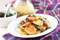 Τηγανισμένο gnocchi πατατών με τη σάλτσα των ξηρών ντοματών, σπανάκι Στοκ Εικόνες