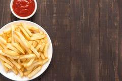 Τηγανιτές πατάτες με το κέτσαπ στο ξύλινο υπόβαθρο στοκ φωτογραφίες