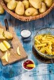 Τηγανιτές πατάτες που γίνονται από τις πατάτες στον μπλε πίνακα Στοκ εικόνες με δικαίωμα ελεύθερης χρήσης