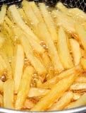 Τηγανιτές πατάτες που τηγανίζονται στο πετρέλαιο Στοκ φωτογραφία με δικαίωμα ελεύθερης χρήσης