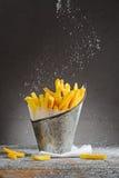 Τηγανιτές πατάτες που ψεκάζονται με το άλας σε έναν κάδο σιδήρου Στοκ Εικόνες