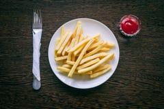 Τηγανιτές πατάτες σε ένα άσπρο πιάτο με το κέτσαπ στοκ φωτογραφίες
