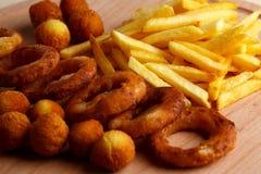 Τηγανιτές πατάτες στον ξύλινο πίνακα Στοκ Φωτογραφία