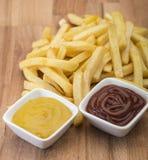 Τηγανιτές πατάτες στον ξύλινο πίνακα με τη σάλτσα catchup & μουστάρδας Στοκ φωτογραφία με δικαίωμα ελεύθερης χρήσης