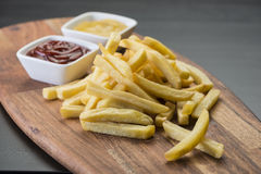 Τηγανιτές πατάτες στον ξύλινο πίνακα με τη σάλτσα catchup & μουστάρδας Στοκ Εικόνες
