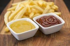 Τηγανιτές πατάτες στον ξύλινο πίνακα με τη σάλτσα catchup & μουστάρδας Στοκ φωτογραφίες με δικαίωμα ελεύθερης χρήσης