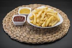 Τηγανιτές πατάτες στο επιτραπέζιο χαλί με τη σάλτσα catchup & μουστάρδας Στοκ Φωτογραφία