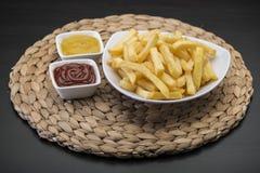 Τηγανιτές πατάτες στο επιτραπέζιο χαλί με τη σάλτσα catchup & μουστάρδας Στοκ Εικόνες