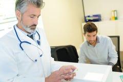 Τηλέφωνο διαβούλευσης γιατρών κατά τη διάρκεια των διαβουλεύσεων με τον ασθενή στοκ φωτογραφία