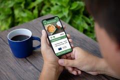 Τηλέφωνο εκμετάλλευσης ατόμων με app τα τρόφιμα σουσιών παράδοσης στην οθόνη Στοκ Εικόνα