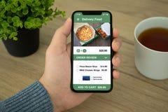 Τηλέφωνο εκμετάλλευσης χεριών ατόμων με app την παράδοση τροφίμων σουσιών Στοκ Εικόνα