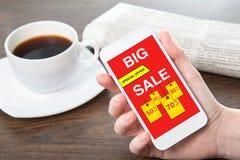 Τηλέφωνο εκμετάλλευσης χεριών γυναικών με τη μεγάλη πώληση στην οθόνη Στοκ φωτογραφία με δικαίωμα ελεύθερης χρήσης