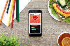 Τηλέφωνο με app την ακολουθώντας οθόνη δραστηριότητας υγείας στον ξύλινο πίνακα Στοκ Εικόνες