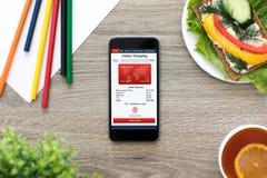 Τηλέφωνο με app τις σε απευθείας σύνδεση αγορές στην οθόνη στον καφέ Στοκ Εικόνες
