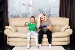 Τηλεοπτικά παιχνίδια παιχνιδιού μητέρων και γιων από κοινού στοκ φωτογραφία