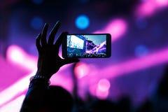 Τηλεοπτική καταγραφή της συναυλίας στο τηλέφωνο smartphone του κόμματος παραλιών στοκ φωτογραφία