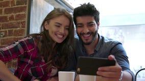 Τηλεοπτική κλήση Ευτυχές ζεύγος που χρησιμοποιεί το τηλέφωνο για την τηλεοπτική κλήση στον καφέ απόθεμα βίντεο