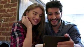 Τηλεοπτική κλήση Ευτυχές ζεύγος που χρησιμοποιεί το τηλέφωνο για την τηλεοπτική κλήση στον καφέ φιλμ μικρού μήκους