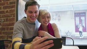 Τηλεοπτική κλήση Ευτυχές ζεύγος στον καφέ που χρησιμοποιεί το τηλέφωνο για την τηλεοπτική συνομιλία απόθεμα βίντεο