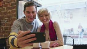 Τηλεοπτική κλήση Ευτυχές ζεύγος στον καφέ που χρησιμοποιεί το τηλέφωνο για την τηλεοπτική συνομιλία φιλμ μικρού μήκους