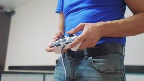Τηλεοπτική κονσόλα χεριών παιχνιδιού τρόπου ζωής έννοιας ατόμων gamepad στη TV Νέο πηδάλιο λαβής χεριών που παίζει την τηλεοπτική απόθεμα βίντεο