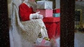 Τηλεοπτική σύνθεση με το μειωμένο χιόνι πέρα από τη συνεδρίαση Santa στον καναπέ στο δωμάτιο απόθεμα βίντεο