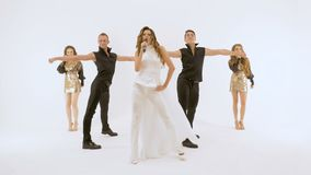 Τηλεοπτικός πυροβολισμός του μουσικού βίντεο Ο κορίτσι-τραγουδιστής σε ένα άσπρο φόρεμα δύο νεαροί άνδρες στα μαύρα κοστούμια χορ φιλμ μικρού μήκους