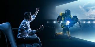 Τηλεοπτικό παιχνίδι αμερικανικού ποδοσφαίρου νεαρών άνδρων παίζοντα στοκ φωτογραφία με δικαίωμα ελεύθερης χρήσης