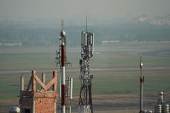 Τηλεφωνική κεραία στην κορυφή στεγών της οικοδόμησης στοκ εικόνα με δικαίωμα ελεύθερης χρήσης