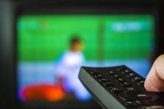 Τηλεχειρισμός TV εκμετάλλευσης χεριών με τη TV στο υπόβαθρο στοκ φωτογραφία