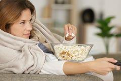 Τηλεόραση προσοχής γυναικών και κατανάλωση popcorn στοκ φωτογραφίες με δικαίωμα ελεύθερης χρήσης