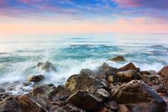 Την άποψη στη θάλασσα και το συμπαθητικό ηλιοβασίλεμα με τον ενδιαφέροντα ουρανό ανοίγουν από την ακτή με τους βράχους Στοκ εικόνα με δικαίωμα ελεύθερης χρήσης
