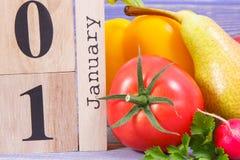 Την 1η Ιανουαρίου ημερομηνίας στο ημερολόγιο και τα φρούτα με τα λαχανικά, έννοια του υγιούς τρόπου ζωής και φαγητό στο νέο έτος Στοκ Φωτογραφίες
