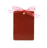 την κόκκινη ετικέττα κορδελλών μονοπατιών δώρων που δένεται ψαλιδίζοντας Στοκ Φωτογραφία